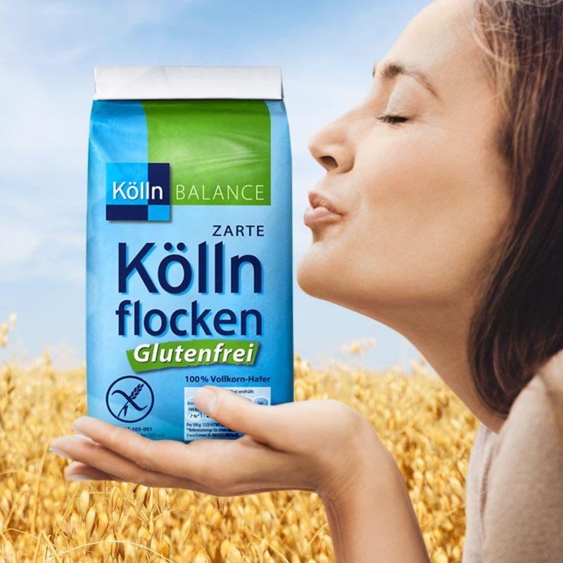 Frau vor Haferfeld deutet Kuss auf Packung mit den glutenfreien Köllnflocken an.