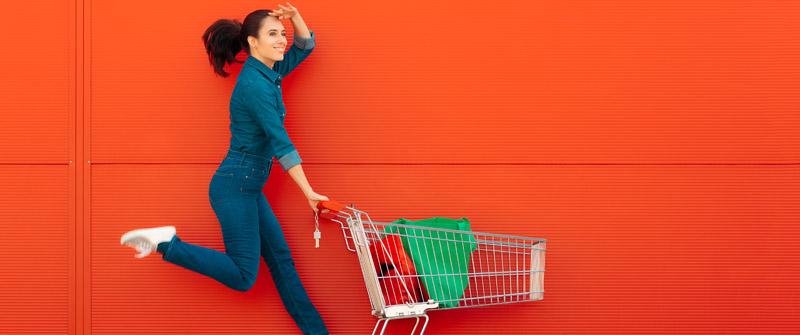 Frau mit Einkaufswagen vor roter Wand