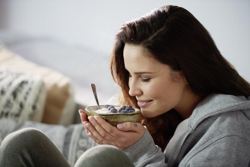 Frau genießt Porridge mit Blaubeeren