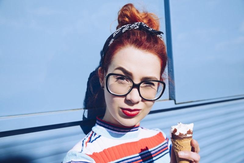 Junge rothaarige Frau lehnt an blauem Minivan und genießt ein Eis.